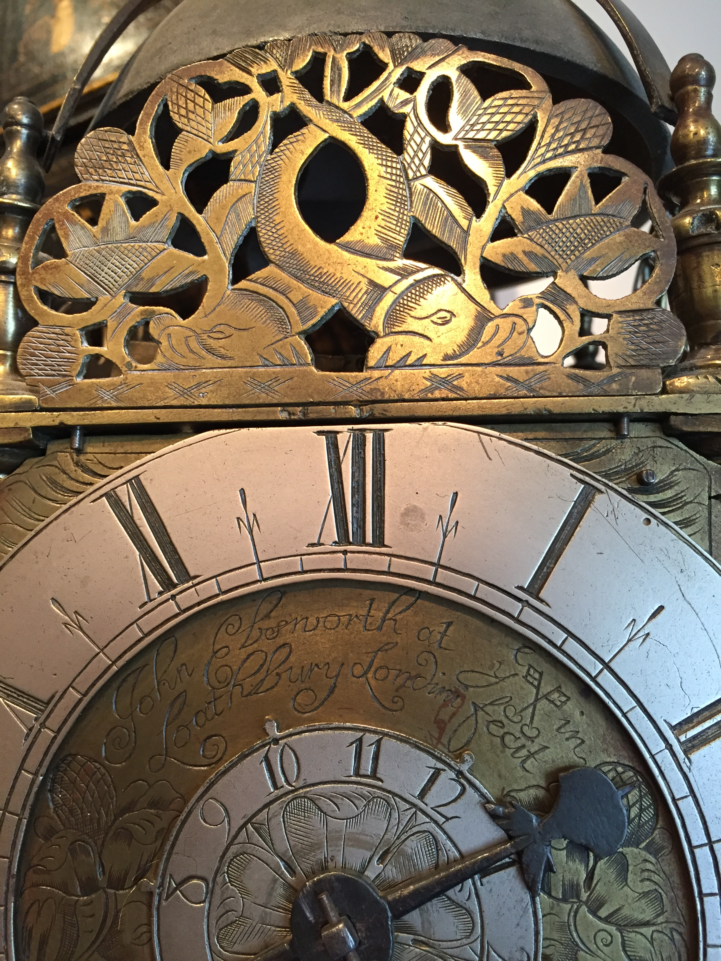 Detail of the Ebsworth lantern clock with engraved dolphin decoration above the signed dial. Raffety Ltd.